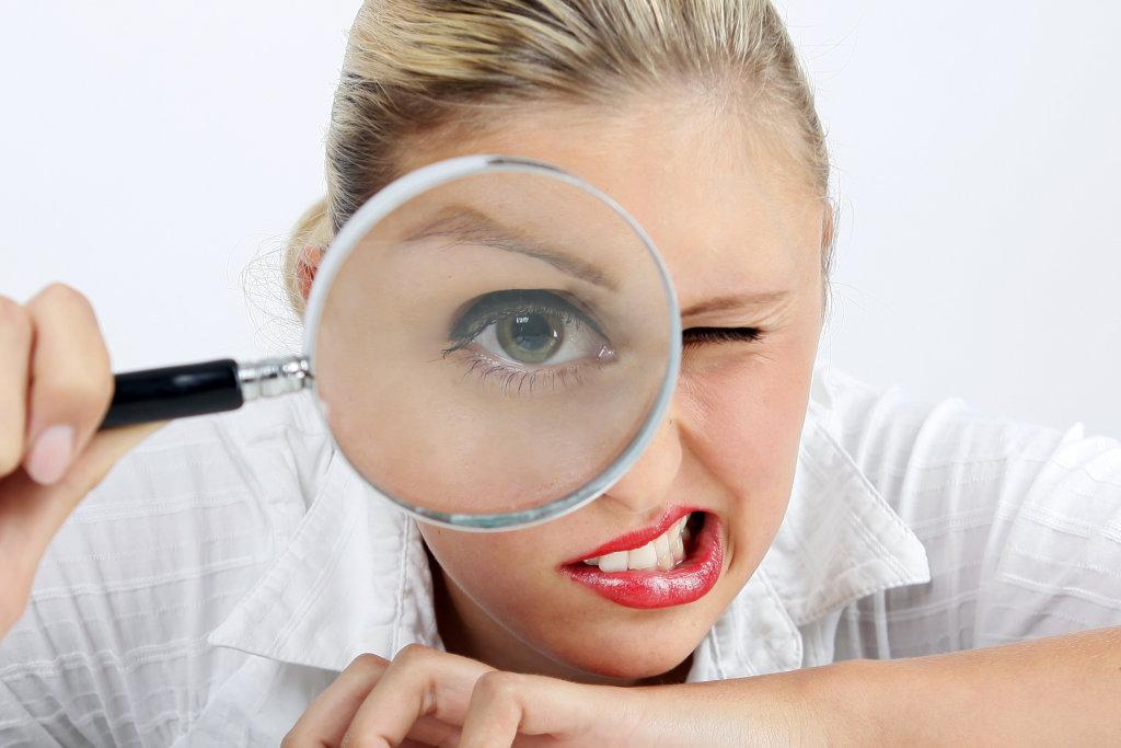 Frau guckt durch eine Lupe