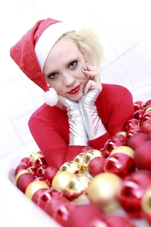 Weihnachtsfrau zwischen Weihnachtskugeln