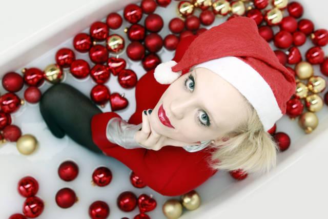 Frau in einer Wanne voller Weihnachtskugeln