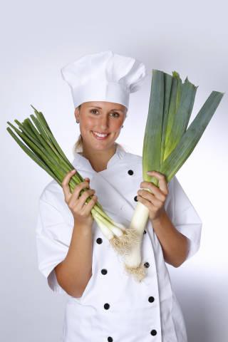 Köchin mit Porree und Lauchzwiebeln