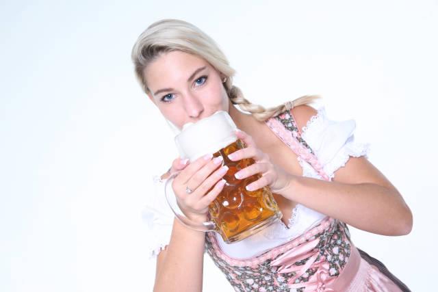 Frau im Dirndl nippt an Bier