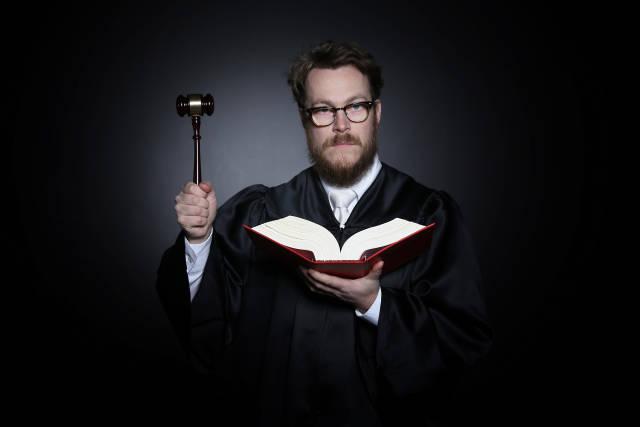 Richter mit Hammer und Gesetzbuch