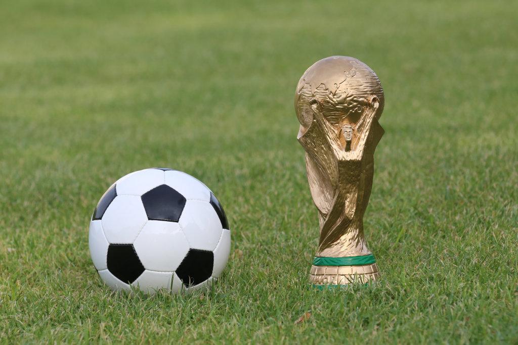 Fußball und WM Pokal auf Rasen