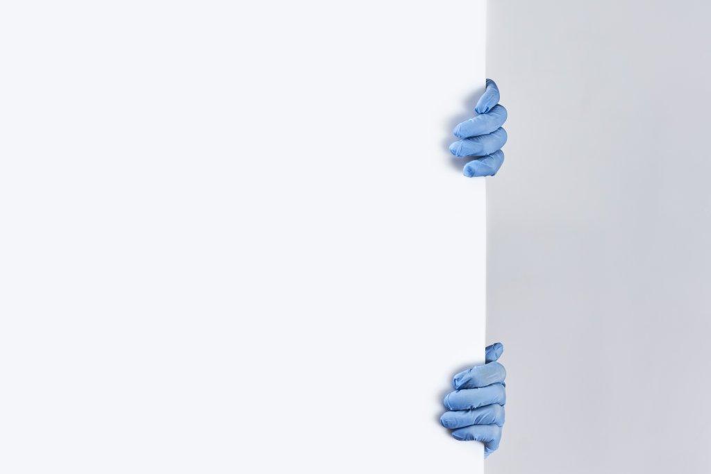 Hinweisschild und Schutzhandschuhe