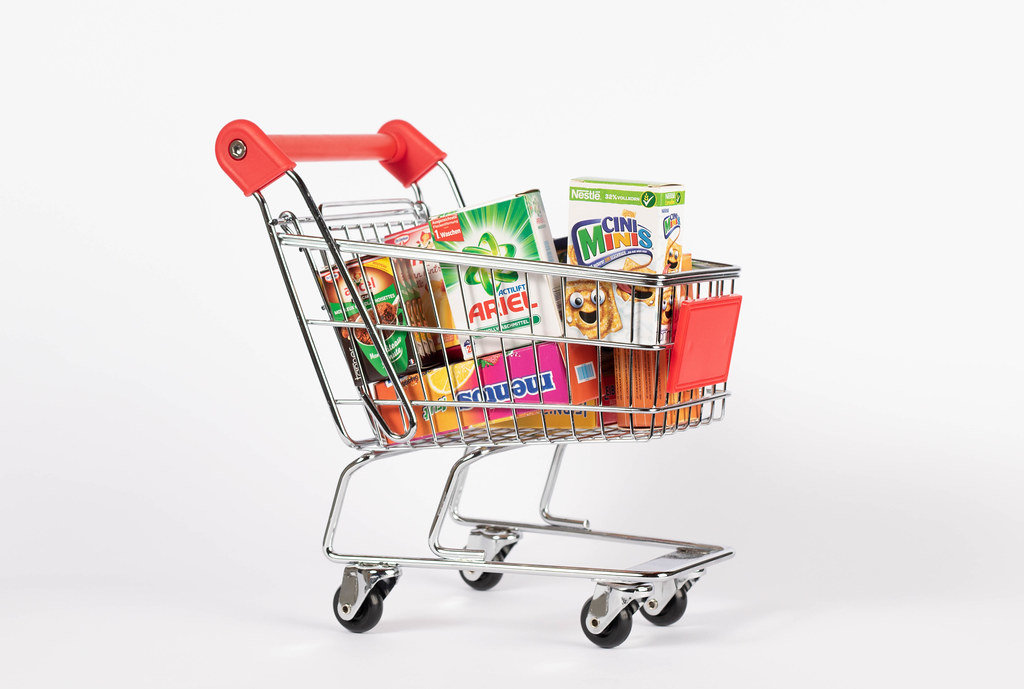 Shopping cart full with various groceries isolated on white