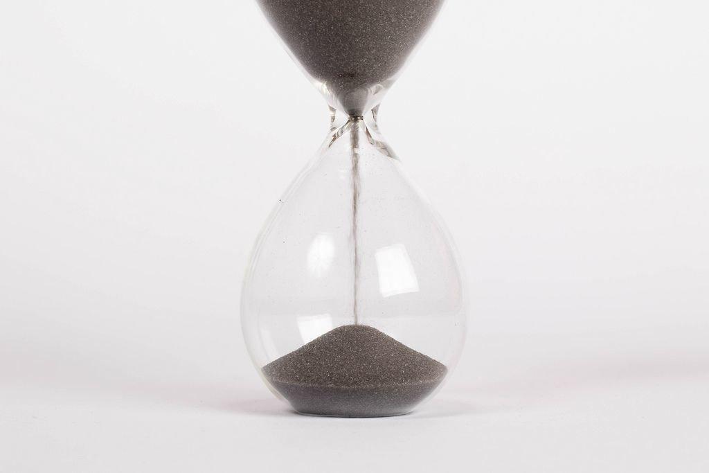 Zeit und Vergänglichkeit – laufende Sanduhr vor weißem Hintergrund