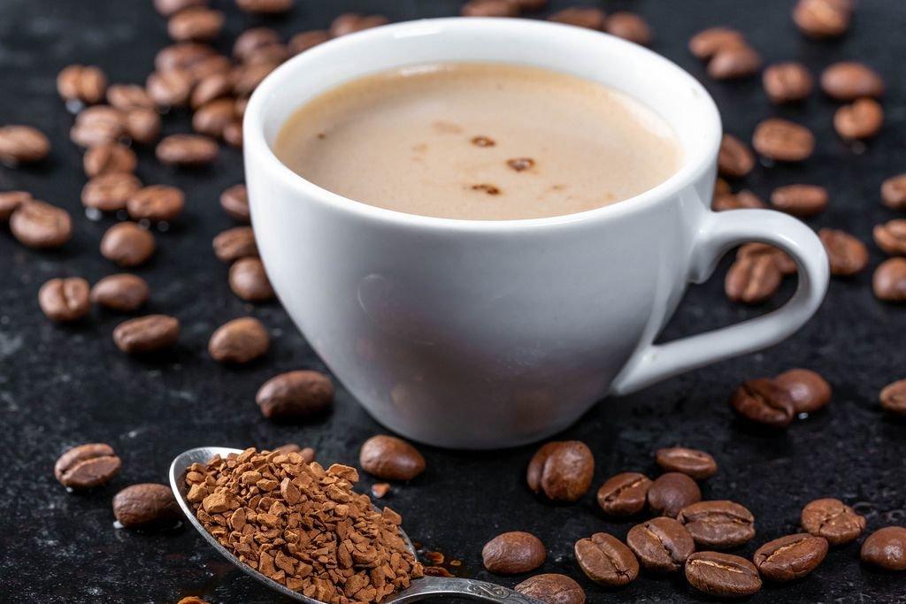Geröstete Kaffeebohnen und heißer Kaffee in einer weißen Tasse auf dunklem Untergrund