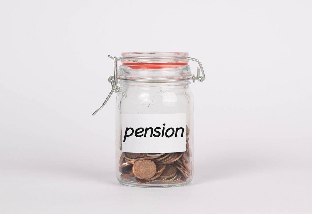 Mit Münzen gefülltes Glas mit Aufschrift PENSION symbolisiert Sparen für Rente
