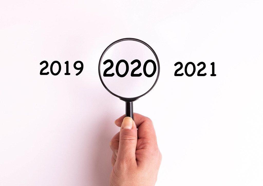 Jahreszahl 2020 auf weißer Oberfläche unter einer Lupe dargestellt