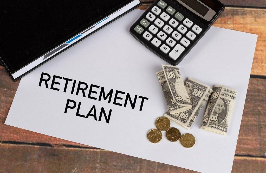 """Ruhestands-Plan""""  auf Papier geschrieben, neben einem schwarzem Notizbuch, Taschenrechner und wenig Geld"""