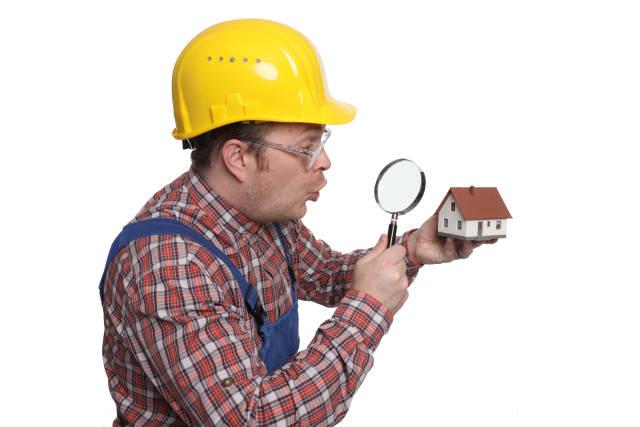 Bauarbeiter mit Lupe und Modellhaus