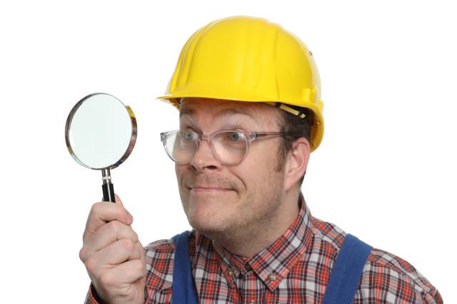 Bauarbeiter mit Lupe