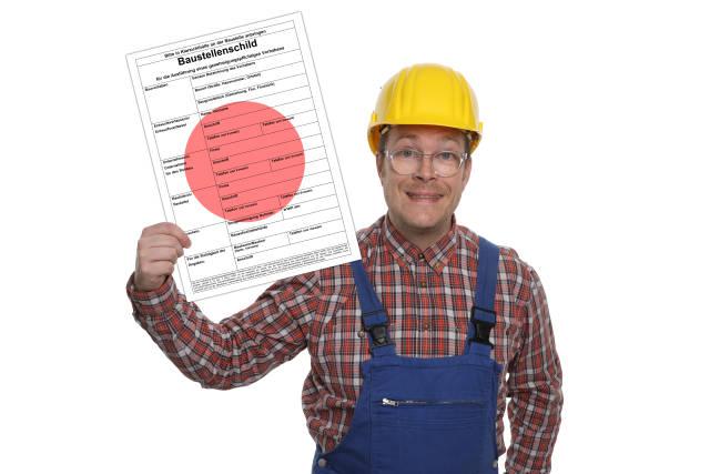 Bauarbeiter hält Baustellenschild