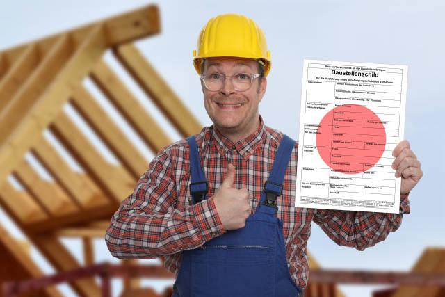 Bauarbeiter mit Baustellenschild