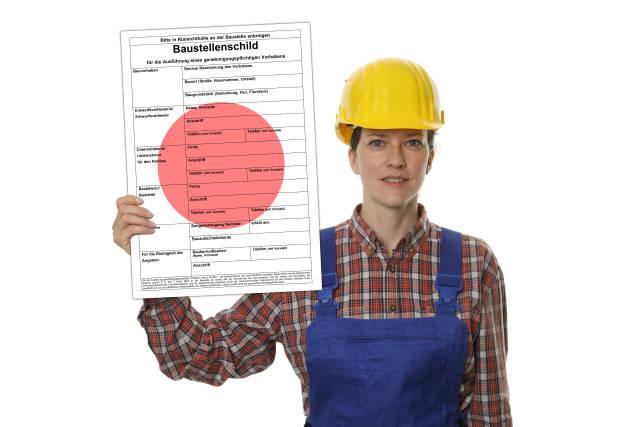 Bauarbeiterin mit Baustellenschild