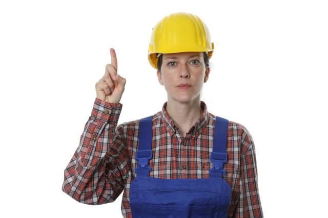 Bauarbeiterin mit erhobenem Zeigefinger