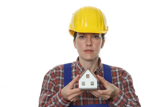 Bauarbeiterin mit Modellhaus