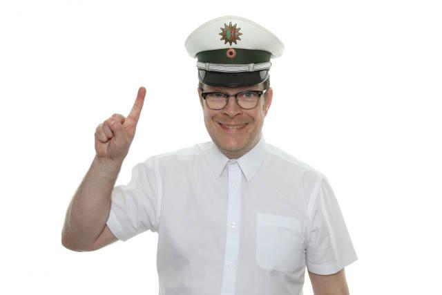 Freundlicher Polizist mit erhobenem Zeigefinger