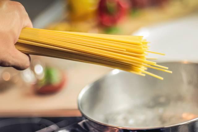 Spaghetti in einen Topf geben