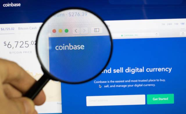 Coinbase-Logo am PC-Monitor, durch eine Lupe fotografiert