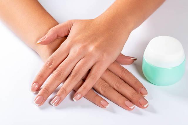 Weibliche Hände mit einer Dose Handcreme auf weißem Hintergrund