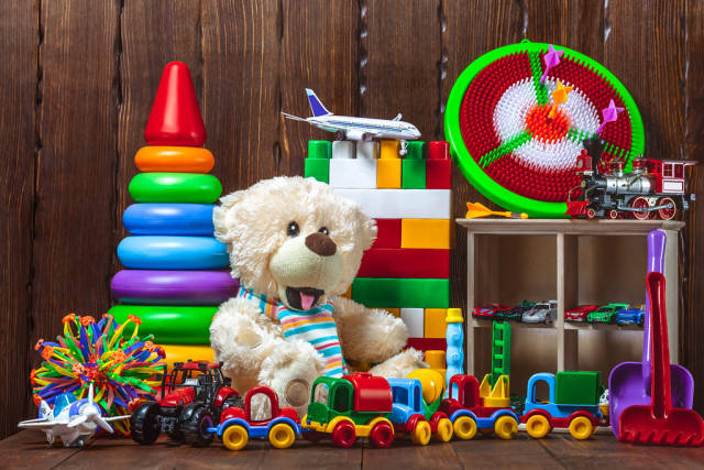 Different childrens toys with a soft bear, cars, a plane, a train and a designer. Concept gifts, happy child