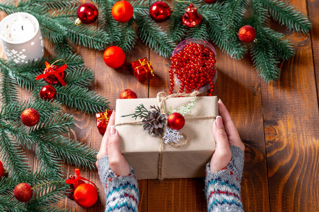 Christmas gift in womens hands with Christmas decor