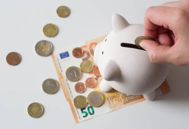 Throwing money into piggy bank