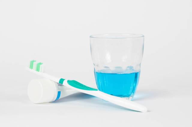 Zahnbürste, Zahnpaste und Mundspülung vor weißem Hintergrund