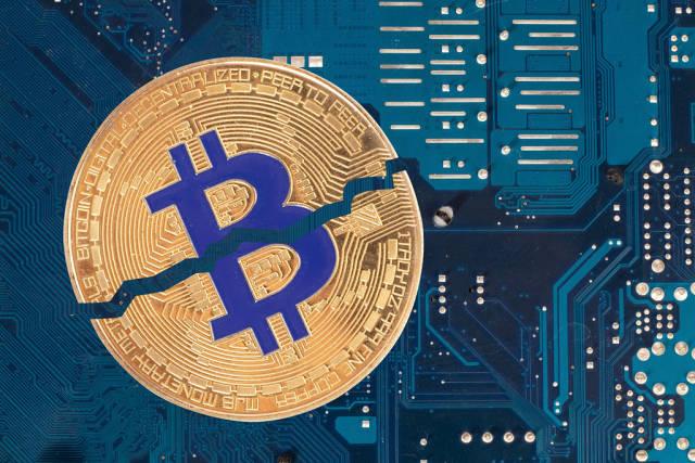 Golden Bitcoin broken in half on computer parts