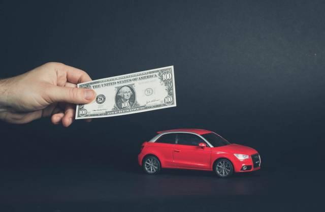 Hand hält Banknote über rotes Auto symbolisiert Sparen und den Kauf eines Autos