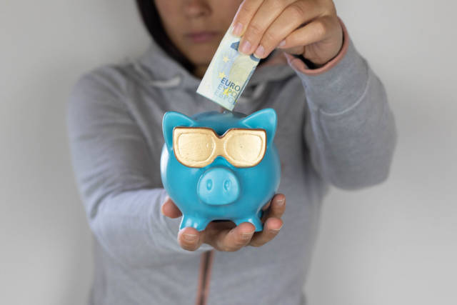 Woman hand putting money bank note into piggy for saving money
