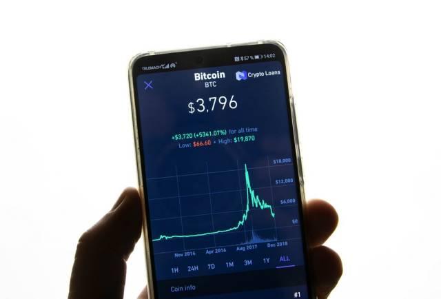 Smartphone zeigt Marktwert von Bitcoin an Aktienmarkt vor weißem Hintergrund