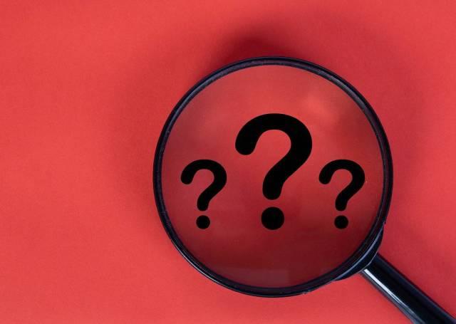 Drei Fragezeichen in schwarz auf rotem Hintergrund, vergrößert unter einer Lupe dargestellt
