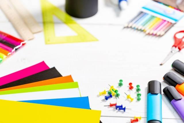 Schulutensilien wie Lineal, Buntstifte, Pinnadeln, Textmarker, Schere, bunte Papierbögen auf Bürotisch