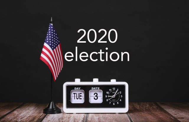 American flag and vintage clock with calendar showing 2020 election date