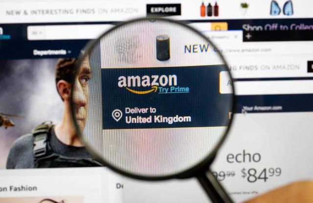 Amazon-Logo am PC-Monitor, durch eine Lupe fotografiert
