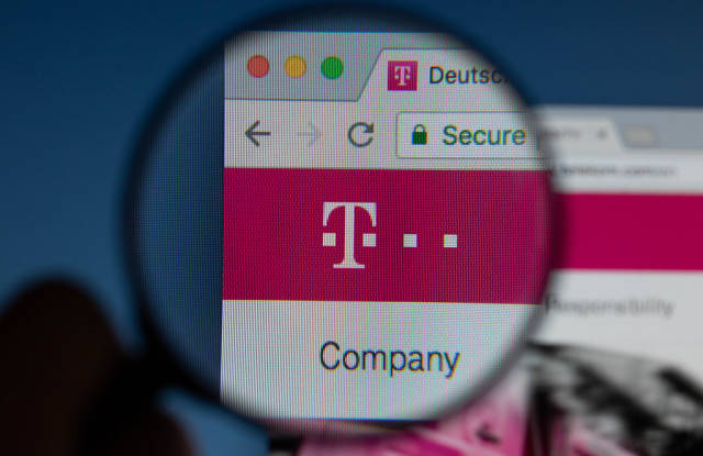 Deutsche Telekom logo on a computer screen with a magnifying glass