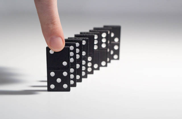 Human hand ready to push a row of dominoes