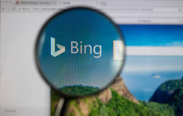 Bing-Logo am PC-Monitor, durch eine Lupe fotografiert