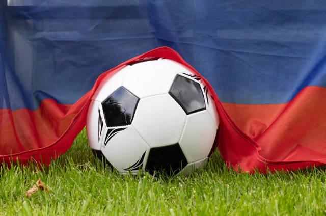Fußball auf dem Rasen bedeckt mit russischer Flagge