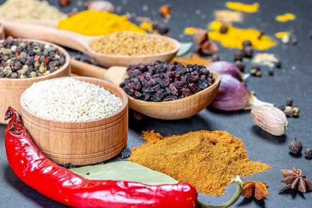Nahaufnahme von verschiedenen Gewürzen - Sesam, rote Chili, und Chilipulver mit Knoblauchzehe  und einer Muskatnuss auf schwarzem Hintergrund