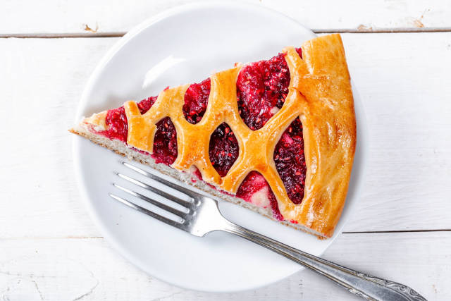 A piece of raspberry pie on a white plate with a fork. Top view