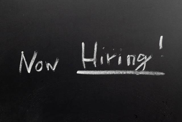 Now hiring written on a black chalkboard