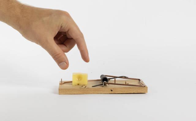 Hand im Begriff sich Käse auf einer Mausefalle zu schnappen