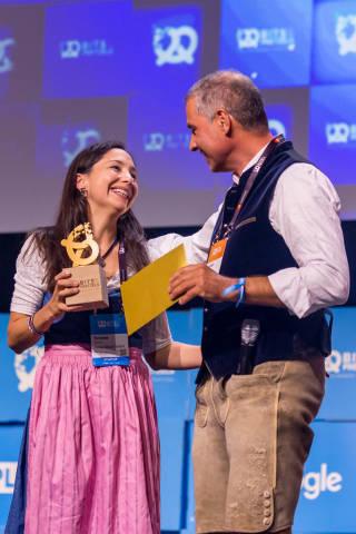 Yvonne Rusche von Münchner Startup Hawa Dawa, das sich dem Thema Luftqualität widmet, bekommt die #bits19 goldene Brezel und bedankt sich bei Andreas Etten von 10x