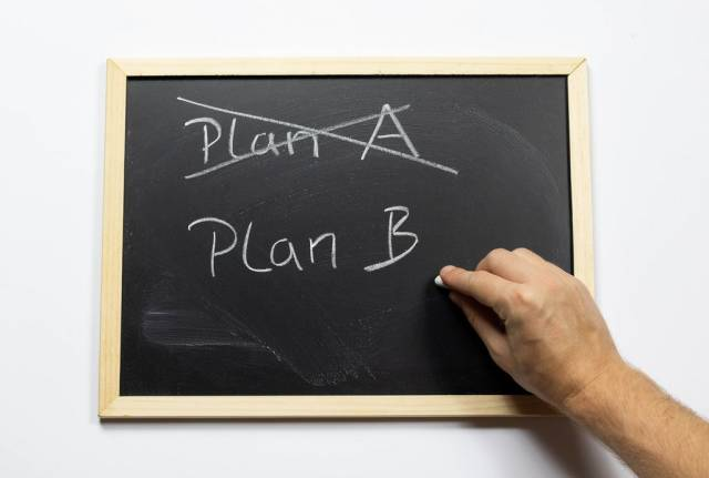 Crossing out Plan A and writing Plan B on a blackboard
