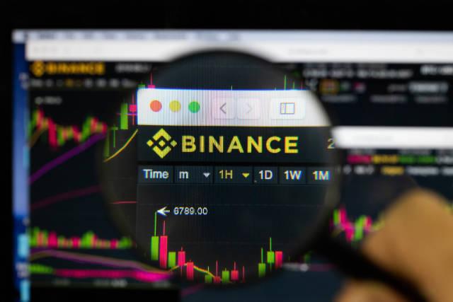 Binance-Logo am PC-Monitor, durch eine Lupe fotografiert