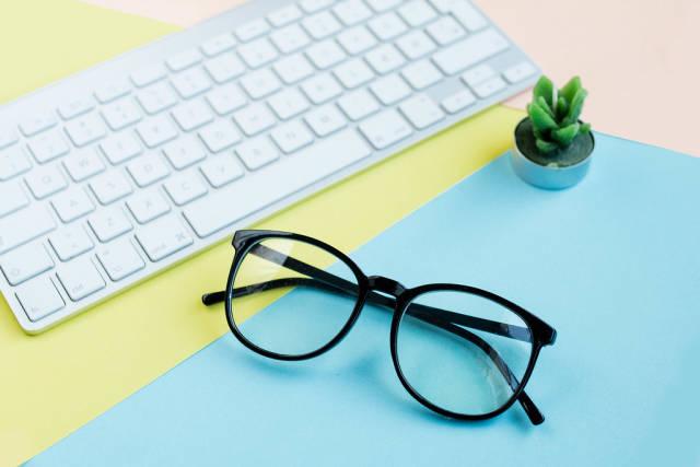 Brille, Tastatur und Kaktus-Kerze vor buntem Hintergrund