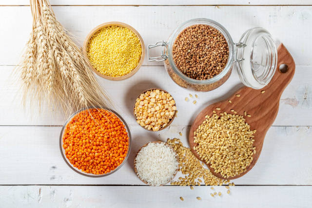 Different cereals: wheat, rice, millet, lentils, peas, buckwheat with spikelets on wooden background